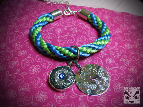 Made this bracelet for a swap. The bracelet is kumihimo, the left charm made with jewelry clay and the right charm is metal stamped.
